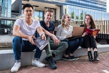 Four law students sitting in front of the REC A building