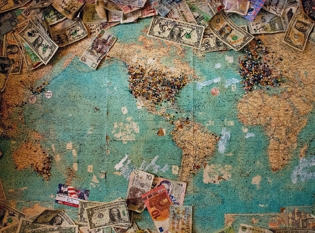World map with several banknotes.